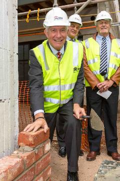 Photo of DHA Chairman, Hon Sandy Macdonald, laying the first bricks at the Prince's Terrace Adelaide site event